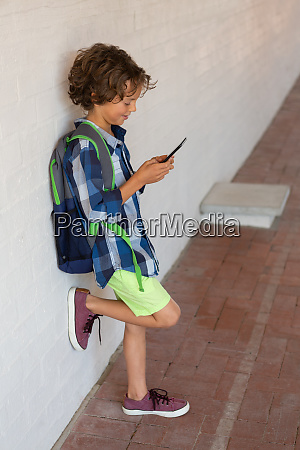 schoolboy using mobile phone in the