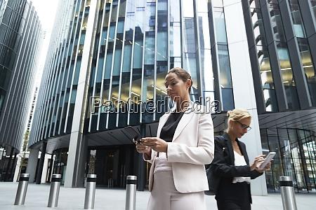 mature businesswomen using smart phones against