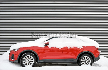 modern red car covered in snow