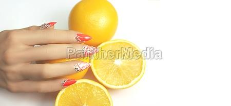 hand with fashion manicure holding orange